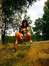 16 pictures - Kinky brunette pissing off a cliff in the woods