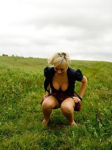 16 pictures - Gorgeous busty blonde filmed pissing on a field